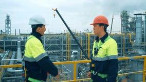 Trabalhadores na planta de produção como a equipe que discute, cena industrial no fundo filme