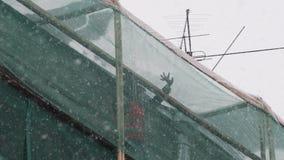 Trabalhadores no suporte uniforme no andaime da construção e para jogar a neve do telhado filme