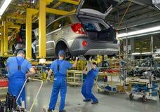 Trabalhadores no transporte de conjunto da planta do automóvel Fotos de Stock Royalty Free