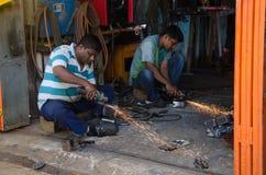 Trabalhadores que cortam detalhes do metal usando a serra elétrica Imagens de Stock Royalty Free