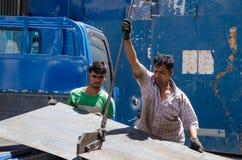 Trabalhadores que cortam uma placa imóvel Imagens de Stock