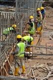 Trabalhadores que fabricam a barra do reforço do feixe à terra Foto de Stock