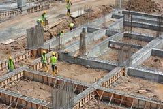 Trabalhadores que fabricam a barra do reforço do feixe à terra Fotografia de Stock Royalty Free
