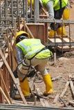 Trabalhadores que fabricam a barra do reforço do feixe à terra Fotos de Stock Royalty Free