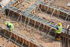 Trabalhadores que fabricam a barra do reforço do feixe à terra Foto de Stock Royalty Free