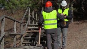 Trabalhadores que falam próximo à trilha de madeira quebrada video estoque