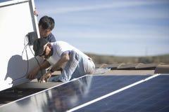 Trabalhadores que fixam o painel solar na parte superior do telhado Imagens de Stock