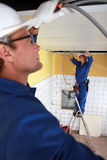 Trabalhadores que instalam a condução por meio de canos Imagem de Stock