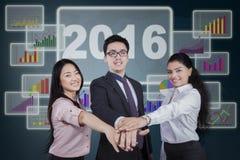 Trabalhadores que juntam-se às mãos na frente da carta financeira Imagens de Stock Royalty Free