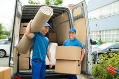 Trabalhadores que levam caixas do tapete e de cartão Fotografia de Stock