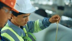 Trabalhadores que medem um tubo com uma fita métrica Terra traseira industrial com pipiline do gás video estoque