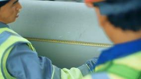 Trabalhadores que medem um tubo com uma fita métrica Terra traseira industrial com pipiline do gás filme