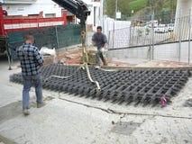Trabalhadores que movem a malha de aço acima do monte íngreme Fotografia de Stock Royalty Free