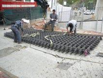 Trabalhadores que movem a malha de aço acima do monte íngreme Fotos de Stock