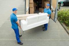 Trabalhadores que põem a mobília e as caixas no caminhão foto de stock royalty free