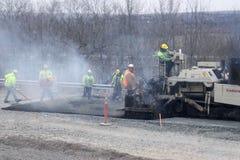 Trabalhadores que pavimentam uma estrada Fotografia de Stock Royalty Free