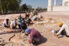 Trabalhadores que reparam a terra exterior de Taj Mahal, Índia Imagem de Stock