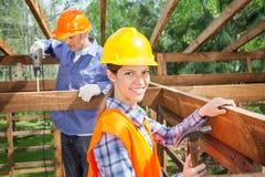 Trabalhadores que trabalham no quadro de madeira no local imagem de stock