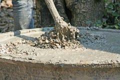 Trabalhadores que usam a enxada para misturar o concreto, a areia, a rocha e a água na bacia plástica preta enorme fotografia de stock