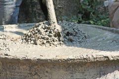 Trabalhadores que usam a enxada para misturar o concreto, a areia, a rocha e a água na bacia plástica preta enorme fotografia de stock royalty free