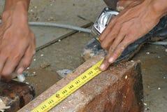 Trabalhadores que usam a fita de medição para medir o aço suave Fotos de Stock Royalty Free
