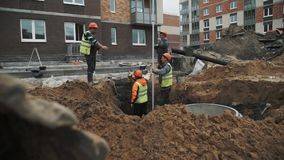 Trabalhadores Slowmotion em capacetes de segurança alaranjados que falam na vala no terreno de construção vídeos de arquivo