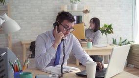 Trabalhadores sonolentos no escritório, um homem e uma mulher que dormem no trabalho, respondendo ao telefone video estoque