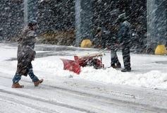 Trabalhando com pá a neve no blizzard Imagens de Stock