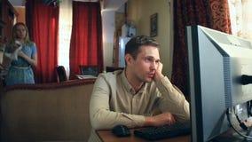 Trabalhando no computador em casa, seu marido é desapontado com a falha do negócio, sua esposa é virado São vídeos de arquivo