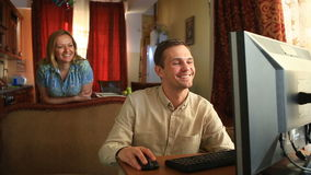 Trabalhando no computador em casa, seu marido é satisfeito com a transação bem sucedida, sua esposa é satisfeito com vídeos de arquivo