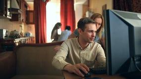 Trabalhando no computador em casa, seu marido está feliz com uma transação bem sucedida, sua esposa e as crianças estão felizes video estoque