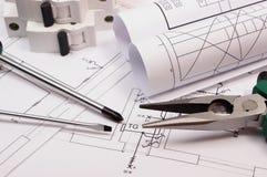 Trabalhe ferramentas, o fusível bonde e os rolos dos diagramas no desenho de construção da casa Imagem de Stock