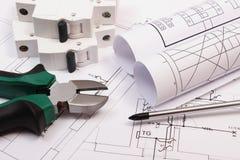 Trabalhe ferramentas, o fusível bonde e os rolos dos diagramas no desenho de construção da casa Fotos de Stock