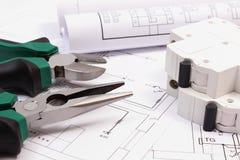 Trabalhe ferramentas, o fusível bonde e os rolos dos diagramas no desenho de construção da casa Foto de Stock Royalty Free