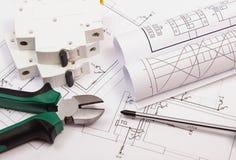 Trabalhe ferramentas, o fusível bonde e os rolos dos diagramas no desenho de construção da casa fotografia de stock