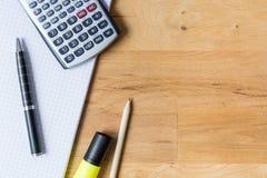 Trabalhe a mesa com almofada de nota, calculadora e biro na tabela de madeira fotografia de stock