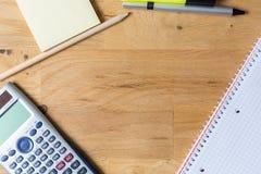 Trabalhe a mesa com almofada de nota, calculadora e biro na tabela de madeira imagens de stock royalty free