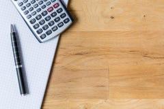 Trabalhe a mesa com almofada de nota, calculadora e biro na tabela de madeira imagem de stock