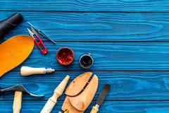 Trabalhe a mesa do sapateiro com instrumentos, a sapata de madeira e o couro Espaço de madeira azul da cópia da opinião superior  imagem de stock