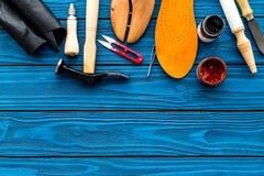 Trabalhe a mesa do sapateiro com instrumentos, a sapata de madeira e o couro Espaço azul da cópia da opinião superior do fundo fotografia de stock
