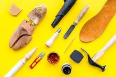 Trabalhe a mesa do sapateiro com instrumentos, a sapata de madeira e o couro Opinião superior do fundo amarelo foto de stock