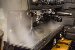 Trabalhe o barista na cafetaria na máquina do café O navio está ligada Vapor quente processar Fundo escuro imagens de stock