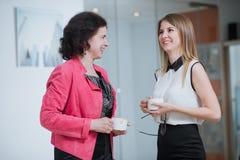 Trabalhe os colegas no escritório que falam entre si durante a ruptura fotos de stock royalty free