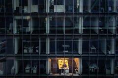 Trabalho atrasado: único escritório iluminado na noite fotografia de stock royalty free