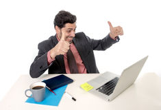Trabalho atrativo do homem de negócios feliz no computador de escritório entusiasmado e eufórico foto de stock royalty free