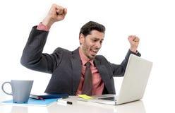 Trabalho atrativo do homem de negócios feliz no computador de escritório entusiasmado e eufórico imagens de stock