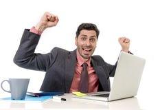 Trabalho atrativo do homem de negócios feliz no computador de escritório entusiasmado e eufórico Foto de Stock