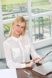 Trabalho bem sucedido Mulher de negócios loura nova que sorri e que guarda a Imagens de Stock