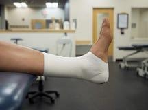 Trabalho da fita do tornozelo em um atleta do time do colégio na clínica imagem de stock royalty free