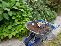 Trabalho da jardinagem e de jarda - carrinho de mão e ancinho imagens de stock royalty free
